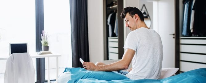 Young man with smartphone in bed at home, text messaging.